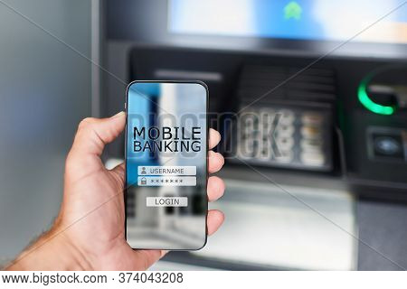 Mobile Banking Concept. A Man Uses The Bank's Mobile Application While Standing Next To An Atm