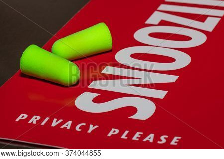 Earplugs On Red Privacy, Snoozing Sign. Snoozing Sign Reads Privacy Please. Sign And One Of The Ear
