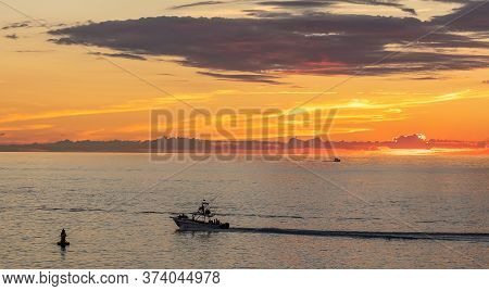 Fishing Boat Sailing At Sunset In Mexico. Beautiful Orange Sky And A Tiny Boat Silhouette In The Bac