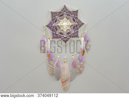 Yarn Mandala With Feathers And Amethyst Beads On Grey Background