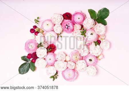 Flowers Composition. Floral Frame Wreath Made Of Roses And Ranunculus Flowers On Pink Background. Fl