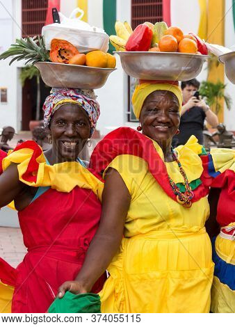 Cartagena, Colombia - January 23th, 2018: Portrait Of Two Palenqueras With A Metal Basket With Fruit