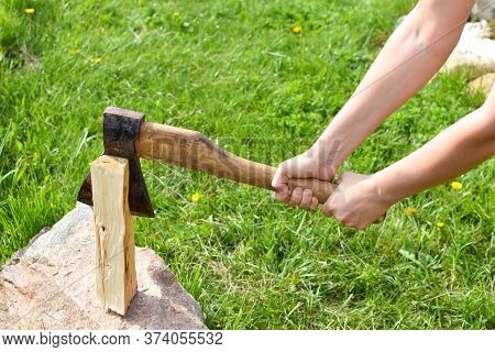 Woman Chopping A Log With An Ax In The Garden. Rural Life In The Summer. Chopping Firewood In The Fr