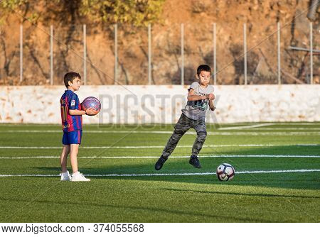 Hydra, Greece - October 4th, 2018: Two Kids Playing Football In A Soccer Field One Of Them With The