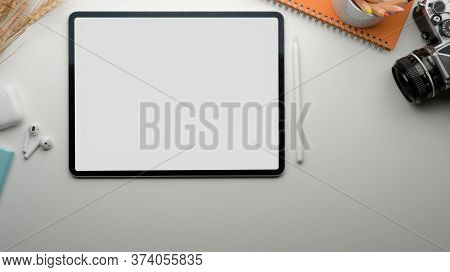 Modern Worktable With Blank Screen Tablet, Tea Cup, Camera, Stationery And Wireless Earphone