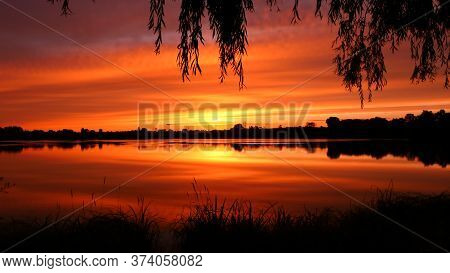 Symmetry Of The Sky In A Lake At Sunrise. Clouds Reflecting On The Water. Holiday Landscape By The S