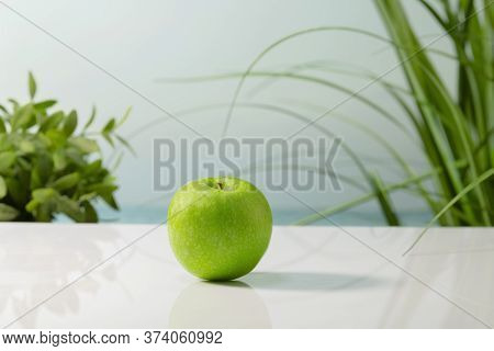 A Delicious Looking Green Apple On A Table On An Out Of Focus Background. Healthy And Vegan Food Con