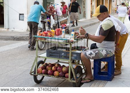 Cartagena, Colombia - January 23th, 2018: A Fruit Street Vendor Looking His Mobile Sitting On His Me