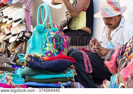 Cartagena, Colombia - January 23th, 2018: A Colombian Craftman Artisan Knitting By Hand Woolen And C