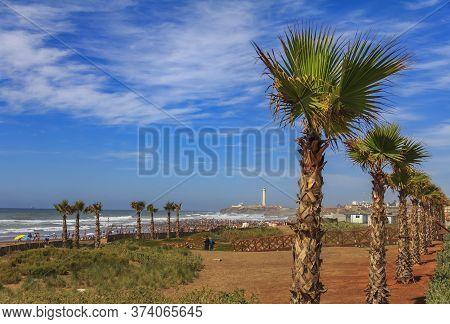 Palm Trees Along The Atlantic Ocean Shore And Unidentifiable People Walking On The Beach With The Li