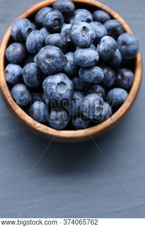 Blueberry Berry In A Wooden Round Cup Close-up On A Black Slate Background.healthy Bio Natural Desse