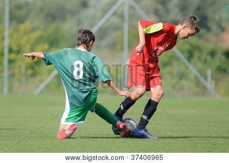 KAPOSVAR, HUNGARY - SEPTEMBER 22: Daniel Galambos (green 8) in action at the Hungarian Championship under 15 game between Rakoczi (green) and Mezga FC (red) September 22, 2012 in Kaposvar, Hungary.