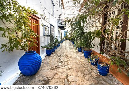 Hydra, Greece - October 4th, 2018: A Narrow Street Perspective With Blue Plants Pots Next The Walls