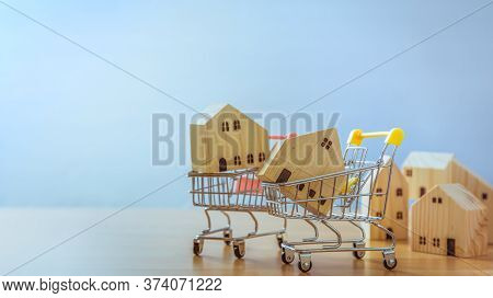 Wooden House In Cart On Wooden Desk. Saving Plan For Residence Of People In Society. Purchasing Home