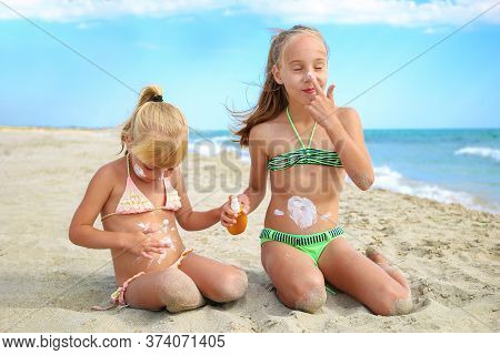 Sister Applying Protective Sunscreen On Young Child. Girl Draws Sun Cream On Her Stomach.