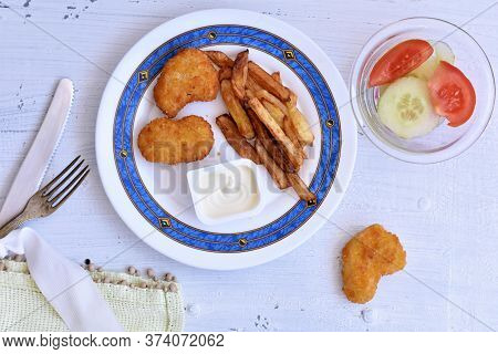 Fried Crispy Chicken Nuggets And French Fries Whit White Sauce Served On White Wooden Background