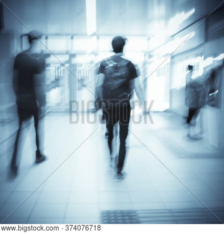 Blurry Image Of Two Young Men Going Out Of A Subway Station. Moving Peiple In Blur.