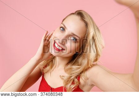 Close Up Of Cute Young Woman In Red Sexy Clothes Posing Isolated On Pastel Pink Background. People L