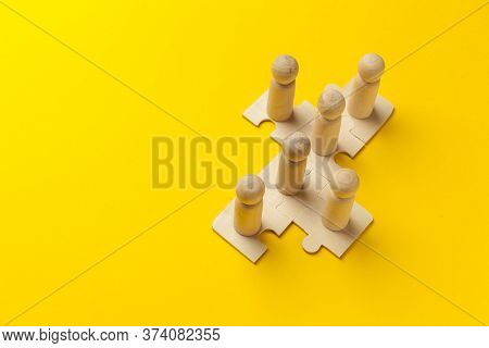 Wooden Figures On Puzzles On Yellow Background As A Symbol Of Team Building. Organization Group Peop
