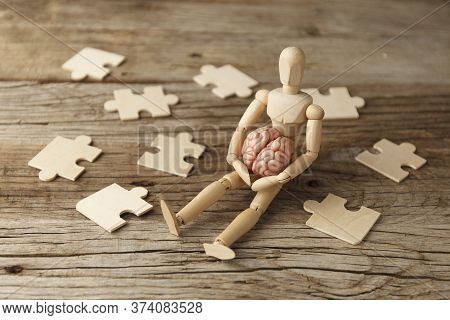 Toy Man Sits Depressed With A Puzzle. Despair And Desolation. Confusion In Itself, Perplexity.