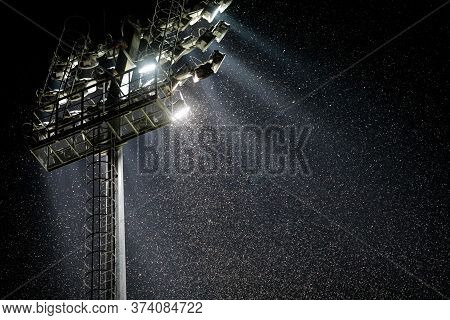 A Swarm Of Mosquitoes And Other Night Insects Fly In The Light Of A Stadium Reflector Near A Big Riv