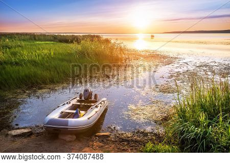 Inflatable Boat On The Lake In The City Of Galich, Kostroma Region And Sunset Sun With Reflection In