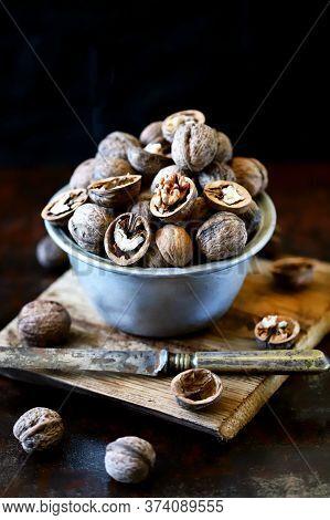 Walnuts In A Bowl On A Dark Background. Unpeeled Walnuts. Inshell Walnuts.