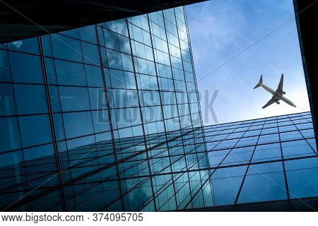 Airplane Flying Above Modern Glass Office Building. Perspective View Of Futuristic Business Building