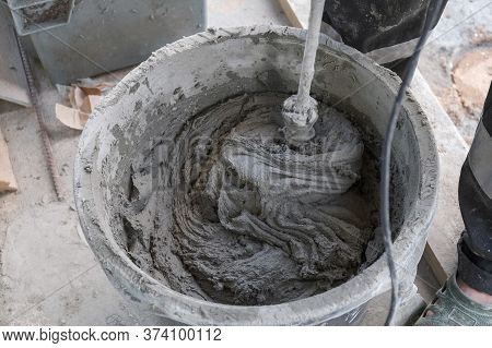 Worker Kneads Cement Mortar In A Bucket