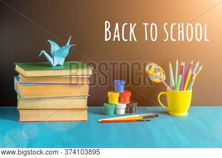 Back To School Text On Black Chalkboard, Books, Stationery In Yellow Mug, Paint Gouache And Origami