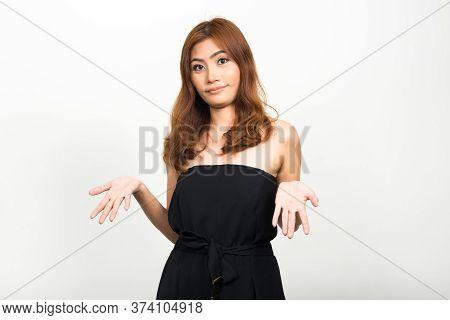 Portrait Of Young Beautiful Asian Woman Shrugging Shoulders