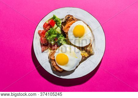 Fried Eggs From Two Eggs On A Pink Background