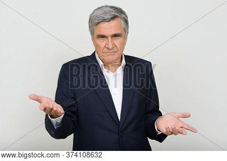 Portrait Of Stressed Senior Businessman In Suit Shrugging Shoulders