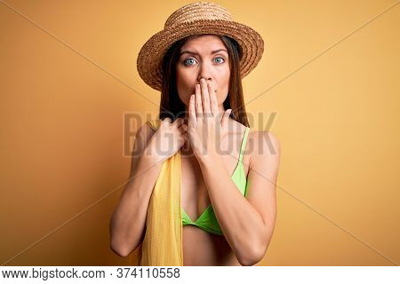 Young beautiful woman with blue eyes on vacation wearing bikini and hat holding towel cover mouth with hand shocked with shame for mistake, expression of fear, scared in silence, secret concept