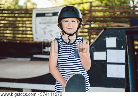Portrait Of Handsome Caucasian Boy Athlete Skateboarder In Protective Helmet With Skateboard In Hand