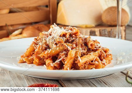 Closeup On Italian Penne Pasta Bolognese With Beef And Parmesan, Horizontal