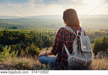 Young Hipster Girl Enjoy Sunset On Viewpoint. Travel Woman With Backpack