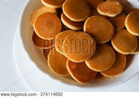 Trendy Food During Coronavirus Quarantine - Pancake Cereal. Mini Pancakes In White Bowl With Butter
