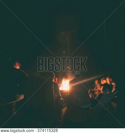 The group of young people are sitting around the bonfire and talking and singing songs