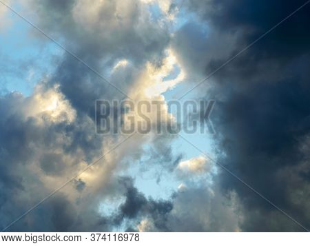 Rift In Gray Clouds. Bright Blue Sky Is Visible Through The Gap In The Dark Clouds. Rain Clouds Surr