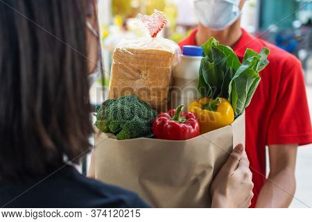 Woman Customer Receiving Fresh Food Set Bag From Food Delivery Service Man With Protection Face Mask