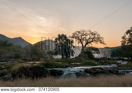 A Baobab Tree At Sunrise On An Island In The Kunene River At The Top Of The Epupa Waterfalls