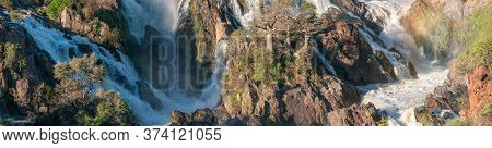 A Stitched Panorama Of Part Of The Epupa Waterfalls In The Kunene River. Baobab Trees Are Visible