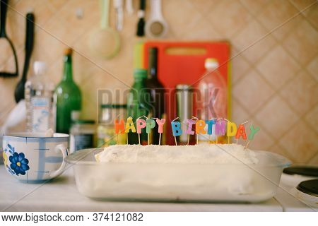 Cake Monastery Izba With Inserted Candles Happy Birthday On The Kitchen Table. Household Amateur Kit