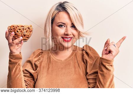 Beautiful plus size woman holding bowl with german baked pretzels over white background smiling happy pointing with hand and finger to the side