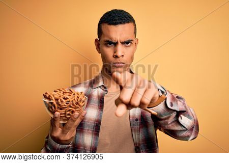 Young handsome african american man holding bowl with german baked pretzels pointing with finger to the camera and to you, hand sign, positive and confident gesture from the front