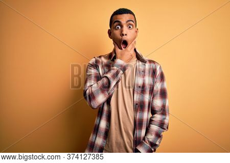 Young handsome african american man wearing casual shirt standing over yellow background Looking fascinated with disbelief, surprise and amazed expression with hands on chin