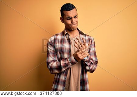 Young handsome african american man wearing casual shirt standing over yellow background Suffering pain on hands and fingers, arthritis inflammation