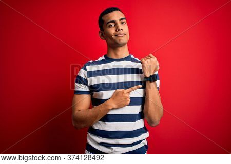 Handsome african american man wearing casual striped t-shirt standing over red background In hurry pointing to watch time, impatience, looking at the camera with relaxed expression