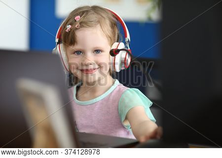 Portrait Of Smiling Girl Looking At Camera With Gladness And Calmness. Happy Baby Playing Computer G